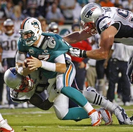 Andre Carter, left, and Mike Wright pull down Dolphins quarterback Chad Henne for a sack last night.
